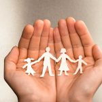 Hands Holding A Paper Cut Out Of A Family
