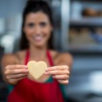 Close Up Of Female Staff Showing Heart Shape Cookie At Counter